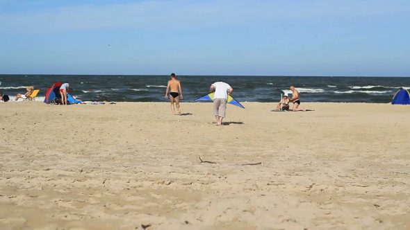 Guys Practicing With A Kite On A Beach