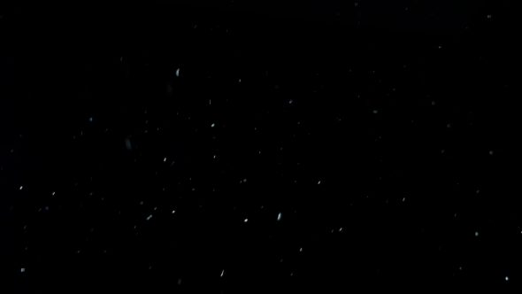 White Dust Particles Flying On Black Underwater Background